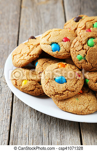 Cookies with colorful candy on plate on grey wooden background - csp41071328