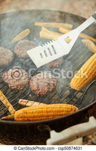 Cooking corn and meat patties over a fire - csp50874631