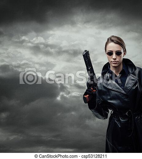Cool female spy holding a gun - csp53128211