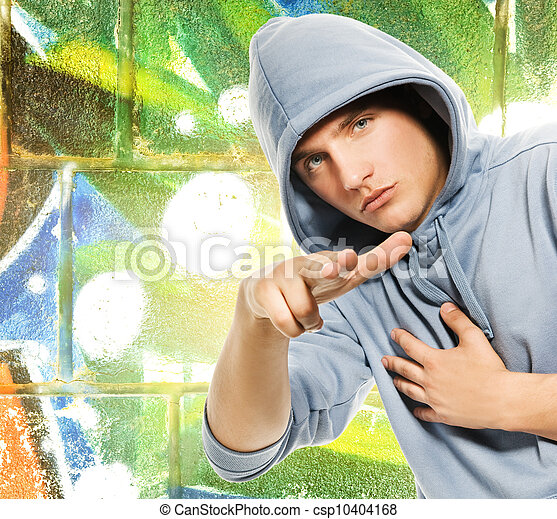 Cool looking man in a hood over abstract graffiti background - csp10404168