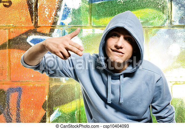 Cool looking man in a hood over abstract graffiti background - csp10404093