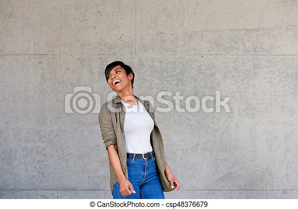 cool young african woman looking over her shoulder - csp48376679