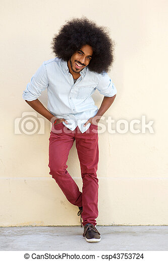 cool young man leaning against wall smiling - csp43753724