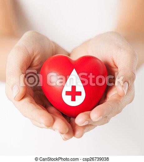 Manos femeninas sosteniendo el corazón rojo con signo de donante - csp26739038