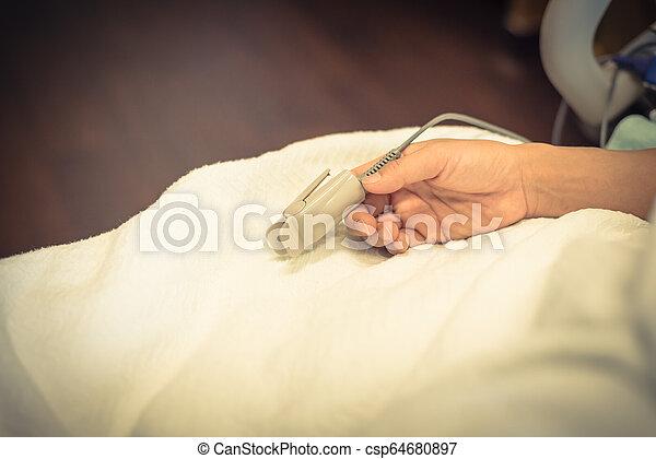 Una mujer con pulso de oxímetro y equipmen de pulso - csp64680897