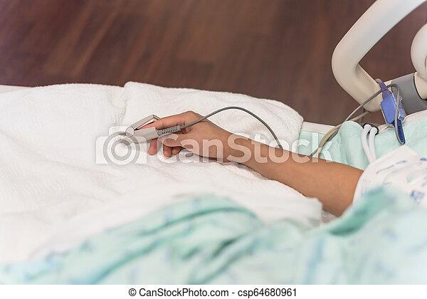 Una mujer con pulso de oxímetro y equipmen de pulso - csp64680961