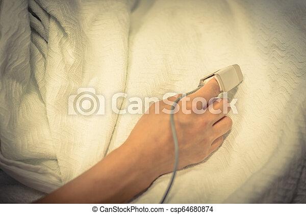 Una mujer con pulso de oxímetro y equipmen de pulso - csp64680874