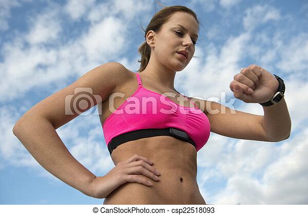 Mujer atlética usando monitor cardíaco - csp22518093