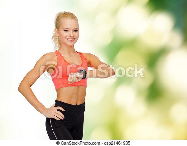 Mujer sonriente con monitor cardíaco a mano - csp21461935