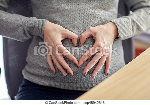 Mujer embarazada haciendo forma de corazón en la oficina - csp45942645