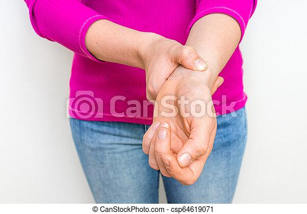Una mujer comprobando el pulso cardíaco en la muñeca - csp64619071