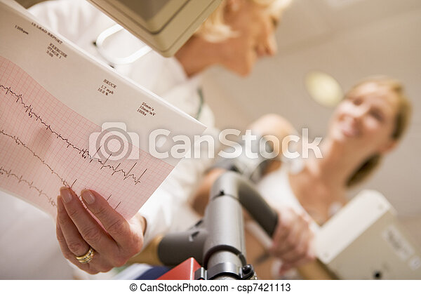 El doctor monitorea el ritmo cardíaco del paciente en una cinta - csp7421113