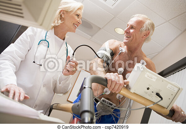 Doctor monitoreando el ritmo cardíaco del paciente en una cinta de correr - csp7420919