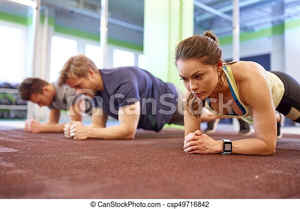 Una mujer con un rastreador de corazón haciendo ejercicio en el gimnasio - csp49716842