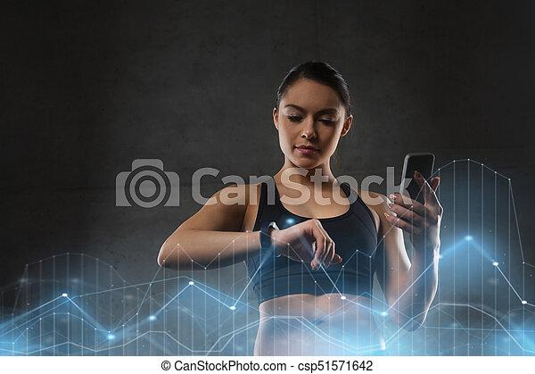 Una mujer con reloj y teléfono inteligente en el gimnasio - csp51571642
