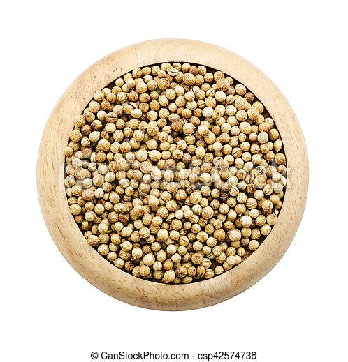 coriander seeds in a wooden dish. - csp42574738