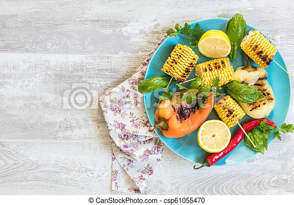 Corn baked in olive oil, with pepper, salt and basil on blue dish on a light surface - csp61055470