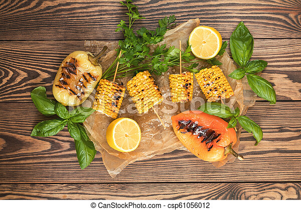 Corn baked in olive oil, with pepper, salt and basil on parchment paper on a dark surface - csp61056012