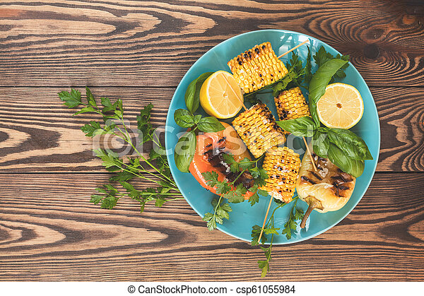Corn baked in olive oil, with pepper, salt and basil on blue dish on a light surface. Vegetarian, vegan menu - csp61055984