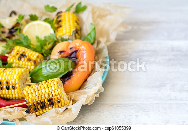 Corn baked in olive oil, with pepper, salt and basil on parchment paper on a dark surface. - csp61055399