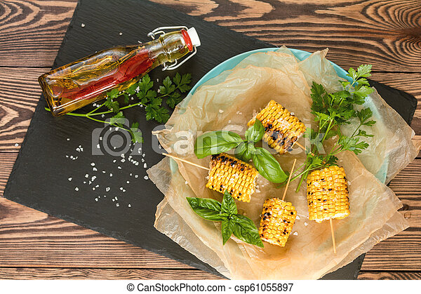 Corn baked in olive oil, with pepper, salt and basil on blue dish on a black stone on dark wooden surface. Vegetarian, vegan menu - csp61055897