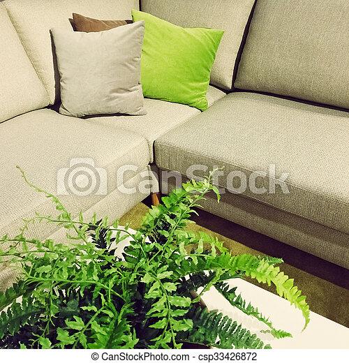 Corner sofa and fern plant decoration - csp33426872