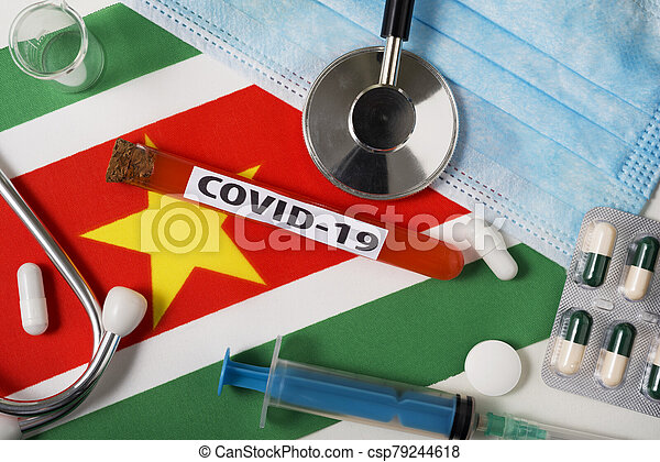 Coronavirus, the concept COVid-19. Top view protective breathing mask, stethoscope, syringe, tablets on the flag of Suriname. - csp79244618