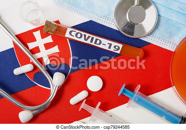 Coronavirus, the concept COVid-19. Top view protective breathing mask, stethoscope, syringe, tablets on the flag of Slovakia. - csp79244585