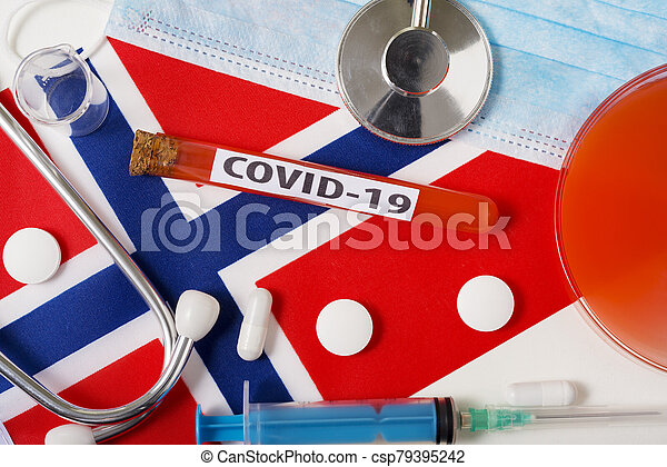 Coronavirus, the concept COVid-19. Top view protective breathing mask, stethoscope, syringe, tablets on the flag of Norway. - csp79395242
