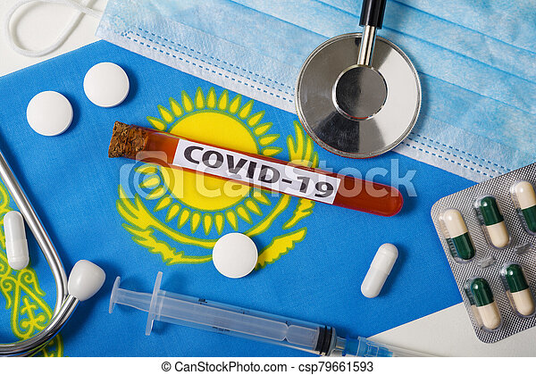 Coronavirus, the concept COVid-19. Top view protective breathing mask, stethoscope, syringe, tablets on the flag of Kazakhstan. - csp79661593