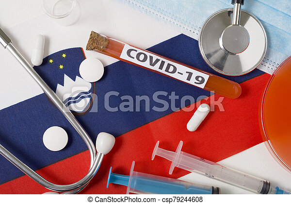 Coronavirus, the concept COVid-19. Top view protective breathing mask, stethoscope, syringe, tablets on the flag of Slovenia. - csp79244608