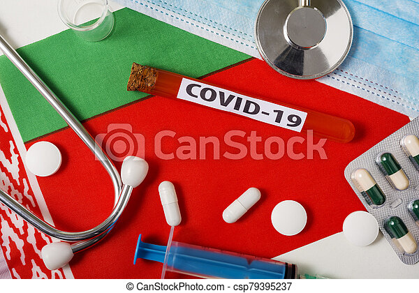 Coronavirus, the concept COVid-19. Top view protective breathing mask, stethoscope, syringe, tablets on the flag of Belarus. - csp79395237
