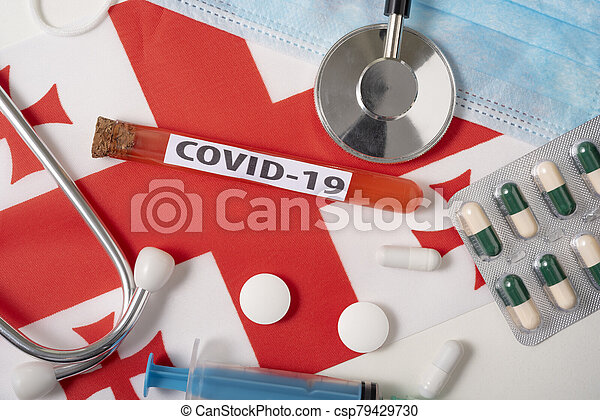 Coronavirus, the concept COVid-19. Top view protective breathing mask, stethoscope, syringe, tablets on the flag of Georgia. - csp79429730