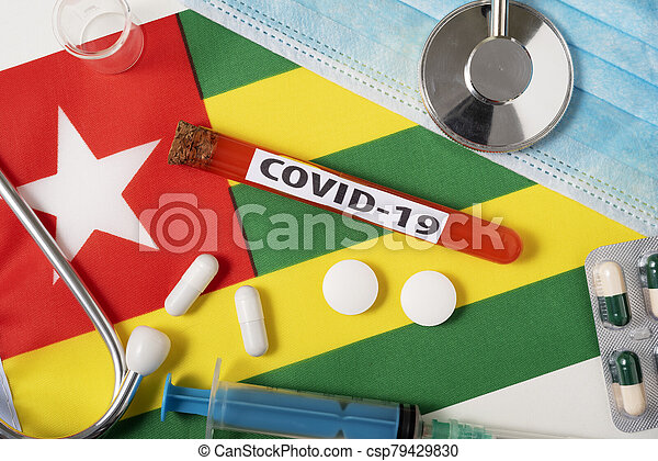 Coronavirus, the concept COVid-19. Top view protective breathing mask, stethoscope, syringe, tablets on the flag of Togo. - csp79429830