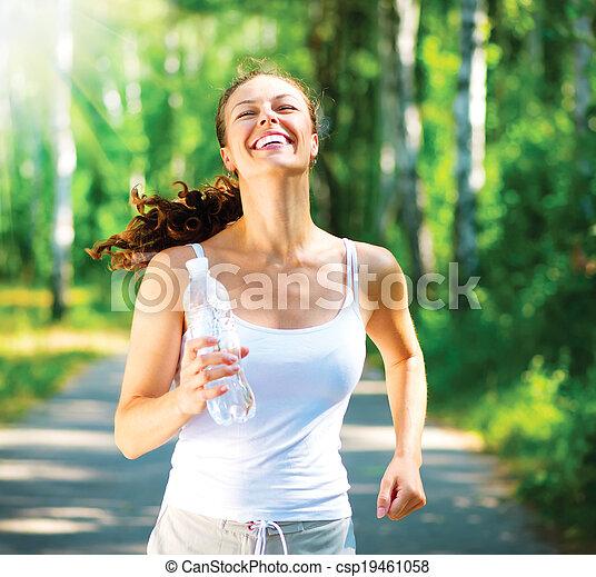 Una mujer que corre. Corredora femenina en un parque - csp19461058