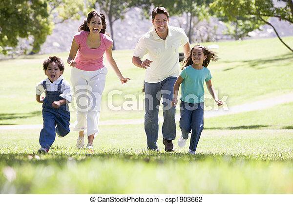 Familia corriendo al aire libre sonriendo - csp1903662