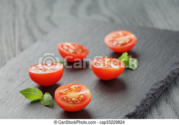 Cortado en mitad de tomates de cereza con hojas de albahaca en pizarra - csp33229824