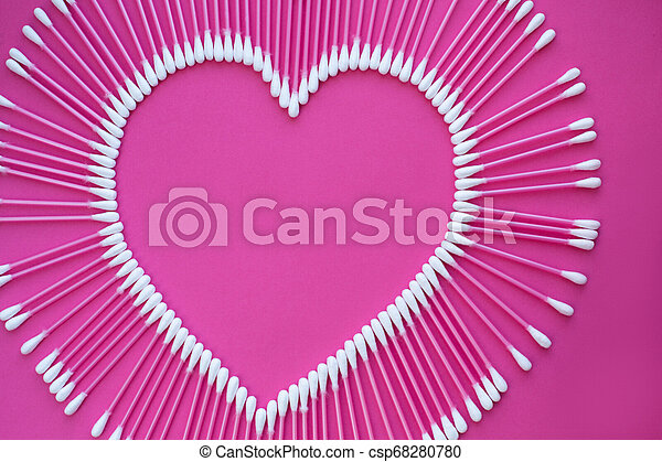 cotton buds laid out in the shape of a heart on a pink background - csp68280780