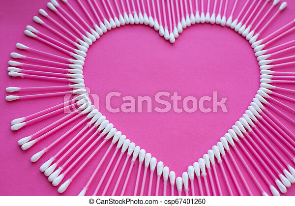 cotton buds laid out in the shape of a heart on a pink background - csp67401260