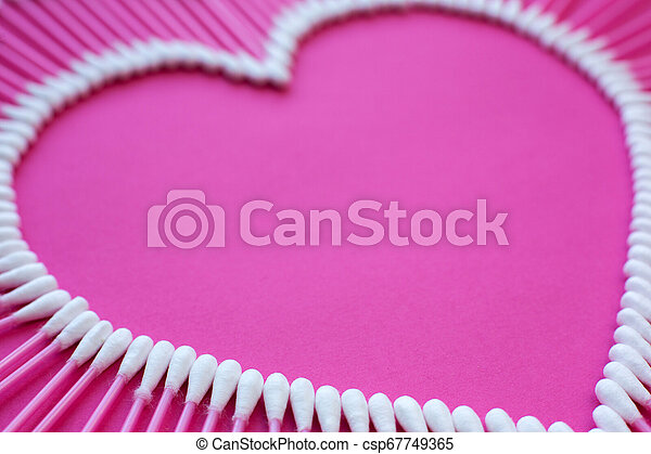 cotton buds laid out in the shape of a heart on a pink background - csp67749365