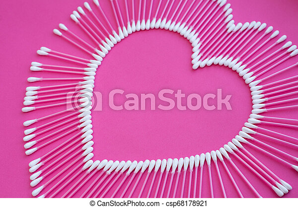 cotton buds laid out in the shape of a heart on a pink background - csp68178921