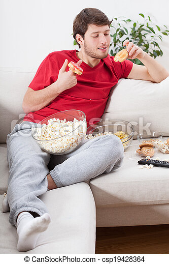 Couch potato eating junk food - csp19428364