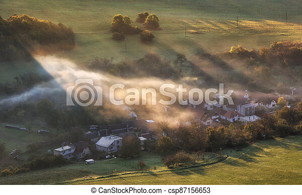 Countryside rural landscape with village over sunbeam in misty morning. - csp87156653
