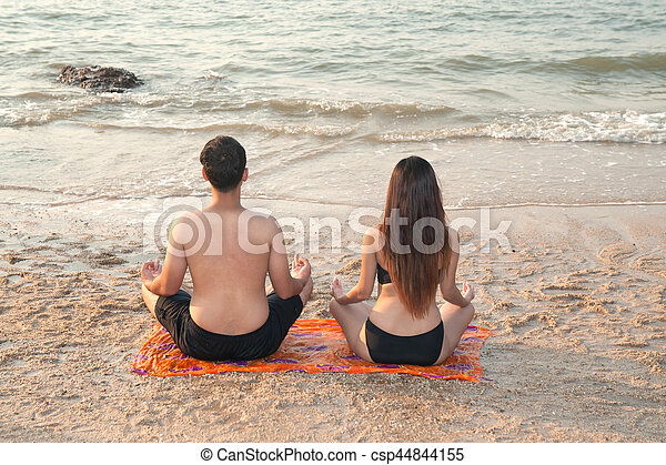 Couple are engaged in fitness yoga exercise on the beach.