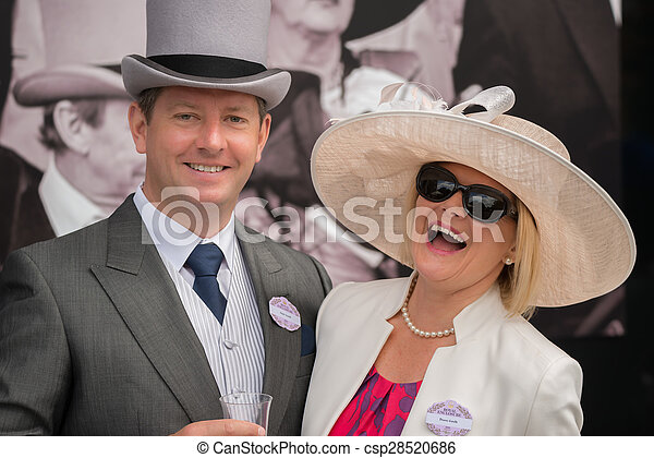 Couple at Royal Ascot laughing at camera - csp28520686