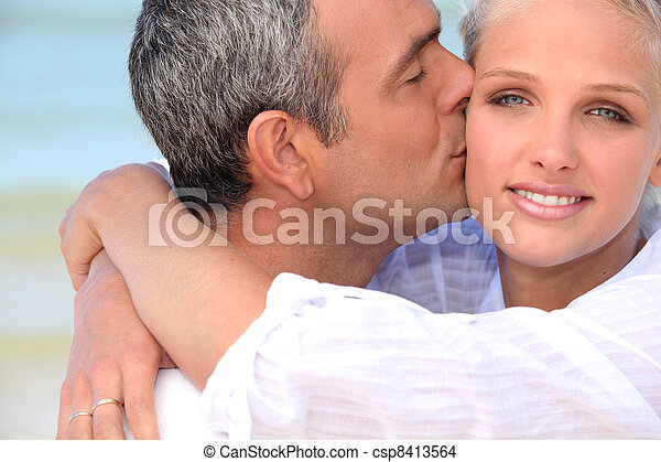 Couple at the beach kissing - csp8413564