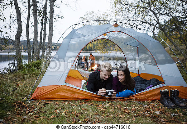 Couple Checking Photos Into Camera While Lying In Tent  sc 1 st  Can Stock Photo & Young couple checking photos into camera while lying in tent ...