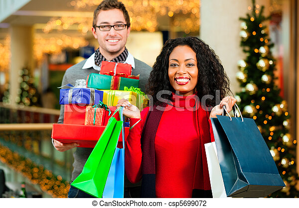 Couple Christmas shopping with presents in mall - csp5699072
