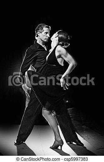 Couple dancing hot latin dance on a street at night - csp5997383