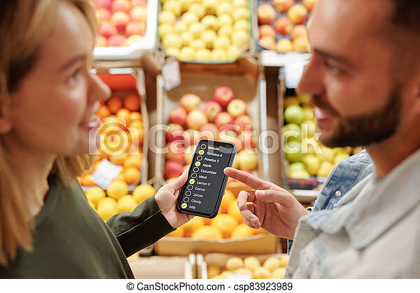 Couple discussing product list at market - csp83923989